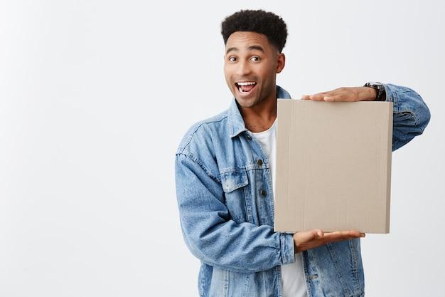 Ritratto di giovane uomo dalla pelle nera divertente allegro con l'acconciatura afro in maglietta bianca sotto giacca di jeans che tiene cartone con espressione faccia felice ed eccitato. copia spazio