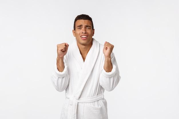 Ritratto di giovane uomo di colore senza camicia bello che sembra eccitato mentre stando contro il bianco