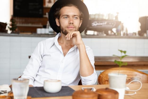 Ritratto di giovane uomo di successo che indossa una camicia bianca e cappello elegante seduto a tavola al ristorante durante il pranzo, con espressione pensierosa o sognante, felice con la sua vita, toccando il mento