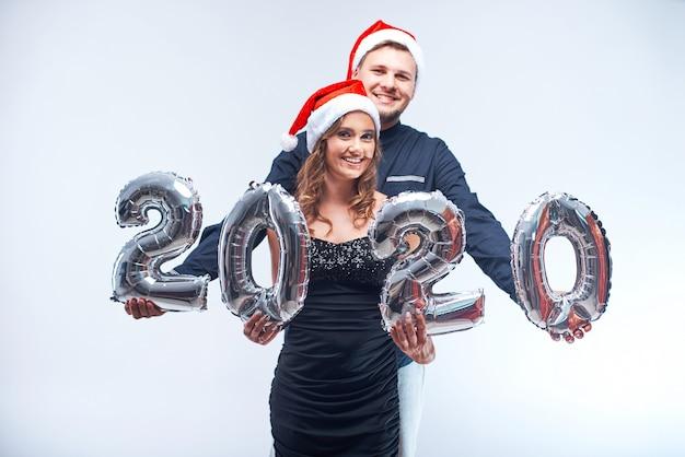 Ritratto di giovane uomo e donna felici in cappelli rossi di santa con i palloni metallici 2020.