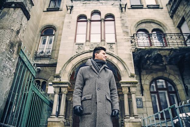 Ritratto di giovane uomo elegante in caldo cappotto grigio e guanti di pelle