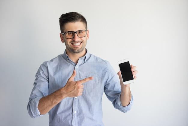 Ritratto di giovane uomo felice in occhiali mostrando il nuovo smartphone.