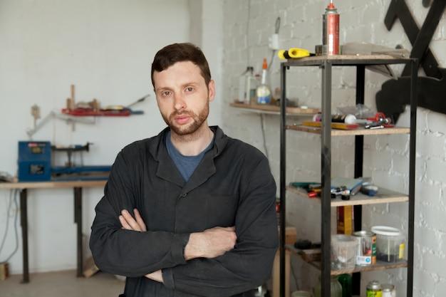 Ritratto di giovane uomo giovane serio in piedi nel proprio interno di laboratorio