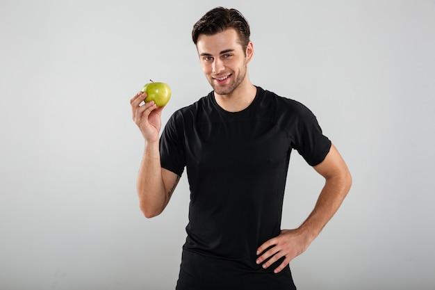 Ritratto di giovane uomo in buona salute che tiene mela verde
