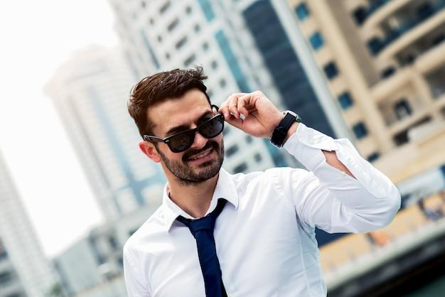 Ritratto di giovane uomo in camicia bianca e cravatta nera