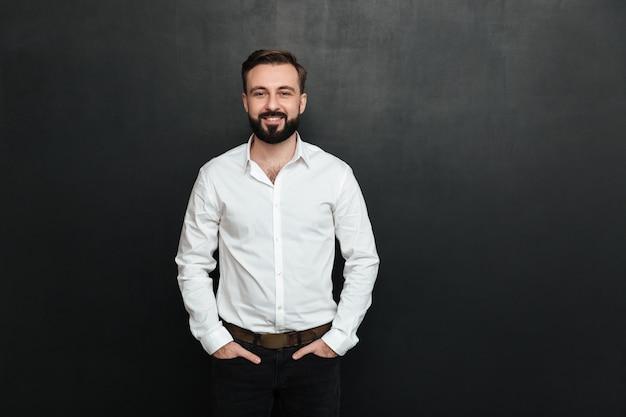 Ritratto di giovane uomo in camicia bianca in posa sulla fotocamera con ampio sorriso e le mani in tasca su grigio scuro
