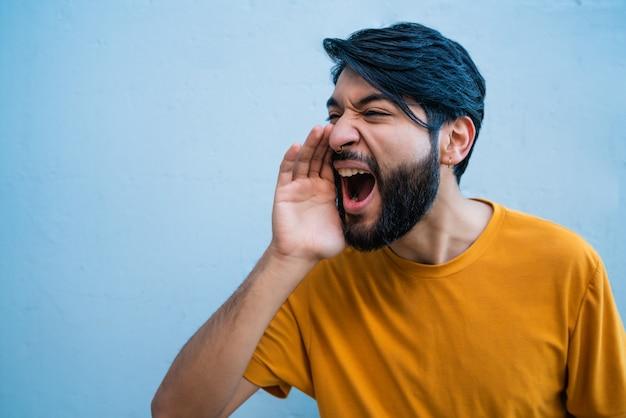 Ritratto di giovane uomo latino che grida e urla contro sfondo blu.