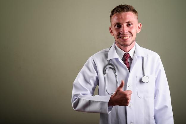 Ritratto di giovane uomo medico contro la parete colorata
