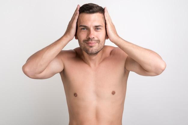 Ritratto di giovane uomo sorridente che tocca i suoi capelli che esaminano macchina fotografica che sta contro il fondo bianco