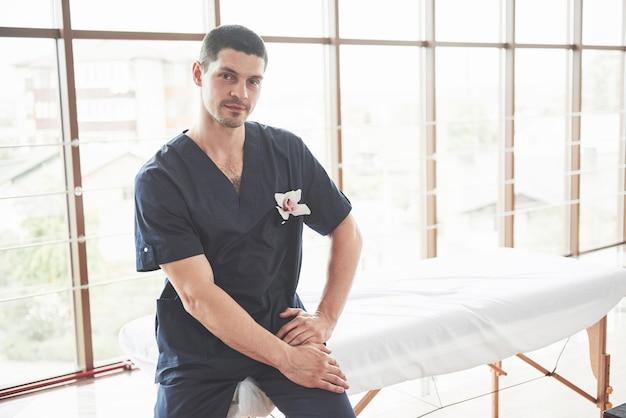 Ritratto di giovane uomo sorridente in uniforme vicino a lettini da massaggio