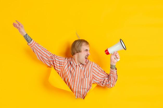 Ritratto di giovane uomo su sfondo strappato giallo strappato