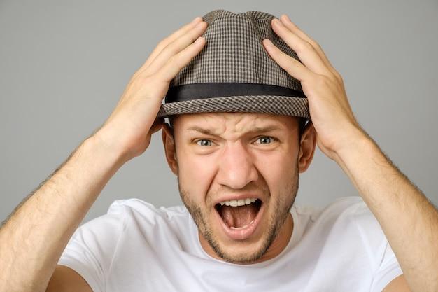 Ritratto di giovane uomo urlando arrabbiato