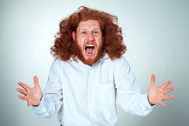 Ritratto di giovane uomo urlando con lunghi capelli rossi ed espressione facciale scioccata sulla parete grigia
