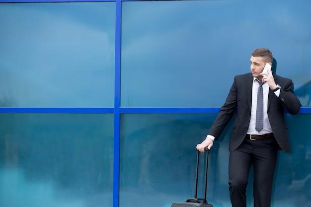 Ritratto di giovane viaggiatore in tuta in piedi con valigia e chiamata. copia spazio