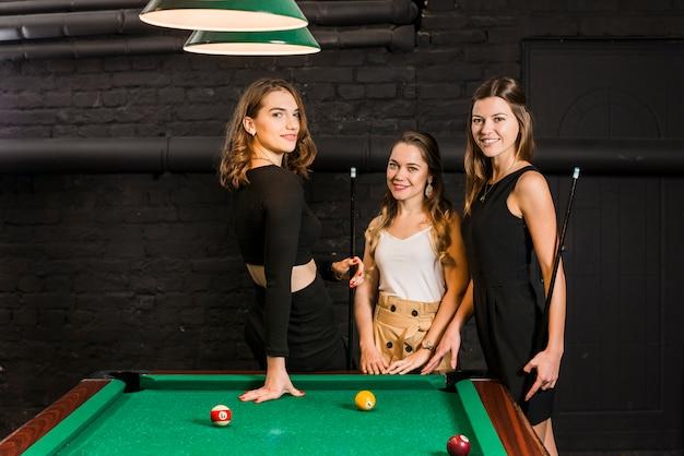 Ritratto di giovani amici femminili sorridenti che stanno vicino alla tavola dello snooker
