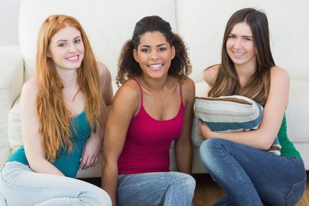 Ritratto di giovani amici femminili sul pavimento contro il divano