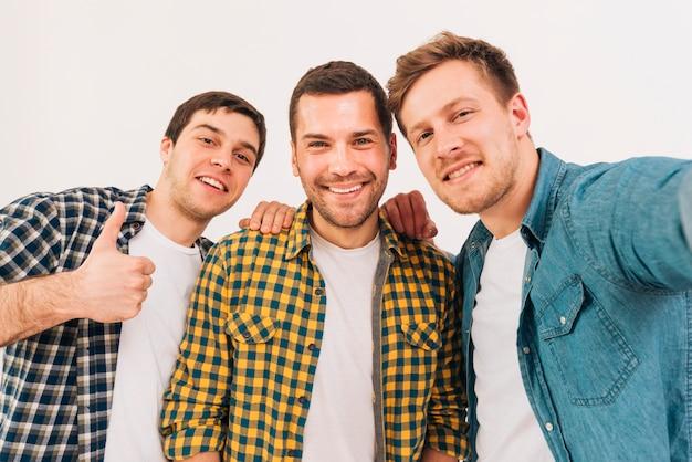 Ritratto di giovani amici maschii sorridenti che esaminano macchina fotografica
