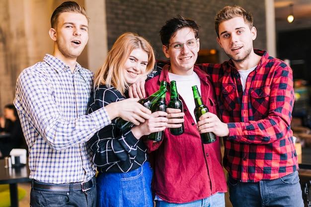 Ritratto di giovani amici sorridenti che tintinnano le bottiglie di birra verde