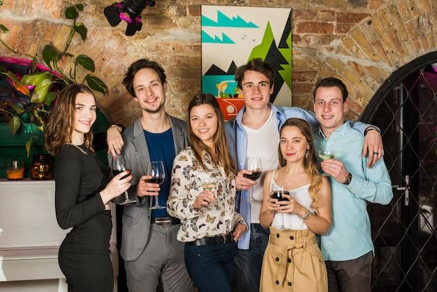 Ritratto di giovani amici tenendo bicchieri di bevande in discoteca