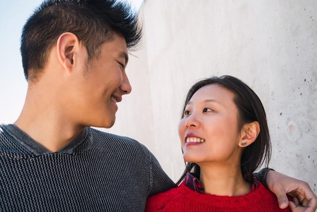 Ritratto di giovani coppie asiatiche nell'amore che abbraccia e che si diverte insieme
