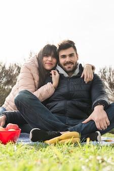 Ritratto di giovani coppie che si siedono con la frutta fresca su erba verde