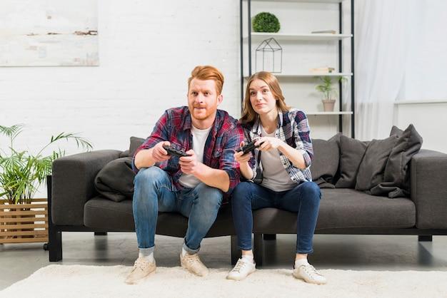 Ritratto di giovani coppie che si siedono sul sofà che gioca il video gioco