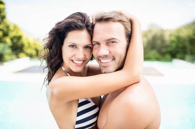 Ritratto di giovani coppie che si stringono a sé vicino allo stagno un giorno soleggiato