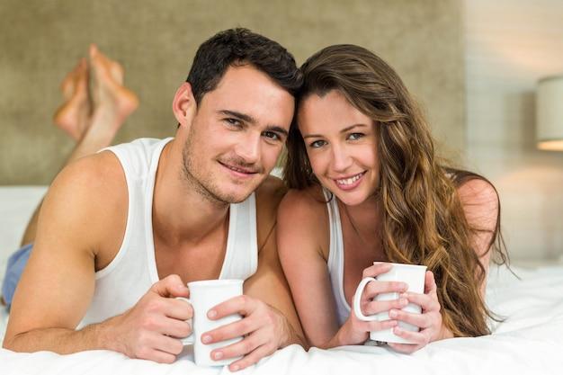 Ritratto di giovani coppie che sorridono e che mangiano tazza di caffè sul letto