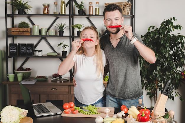 Ritratto di giovani coppie che tengono peperoncino rosso rosso sopra il naso nella cucina