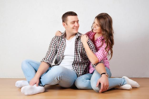 Ritratto di giovani coppie felici che si siedono sul pavimento che osserva in su pronto per il vostro testo o prodotto