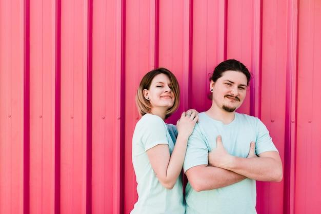Ritratto di giovani coppie felici che stanno contro la lamina di metallo ondulata rosa