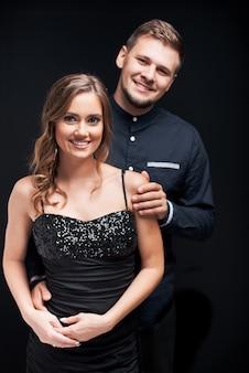 Ritratto di giovani coppie in vestiti da sera eleganti isolati sul nero