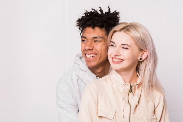Ritratto di giovani coppie interrazziali sorridenti isolate contro priorità bassa bianca