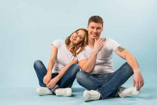 Ritratto di giovani coppie sorridenti che si siedono sul contesto blu