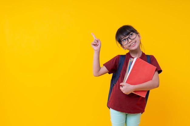 Ritratto di giovani libri asiatici della tenuta della studentessa che indicano su, bambino tailandese grazioso in camicia rossa con la borsa di scuola che cerca e sorriso