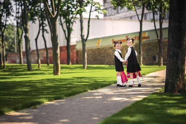 Ritratto di giovani ragazze sorridenti caucasiche felici che indossano lo zaino della scuola fuori della scuola elementare.