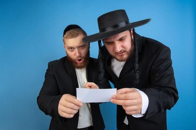 Ritratto di giovani uomini ebrei ortodossi isolati sullo studio blu