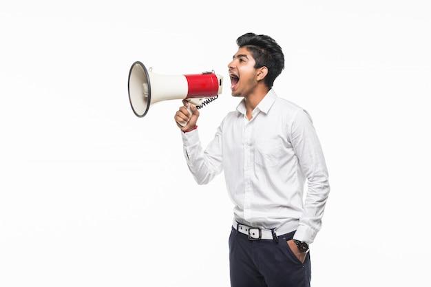 Ritratto di gridare bello del giovane facendo uso del megafono isolato sulla parete bianca