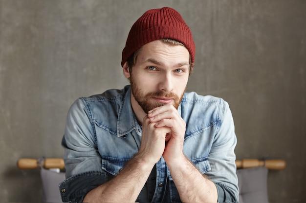 Ritratto di hipster barbuto di bell'aspetto con sorriso amichevole e occhi gentili seduto da solo nel moderno interno della caffetteria, in attesa di amici contro il muro di cemento grigio