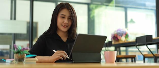 Ritratto di impiegato femminile che lavora con la compressa nella caffetteria