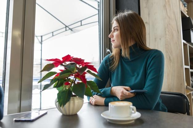 Ritratto di inverno della donna che si siede al caffè con la tazza di caffè