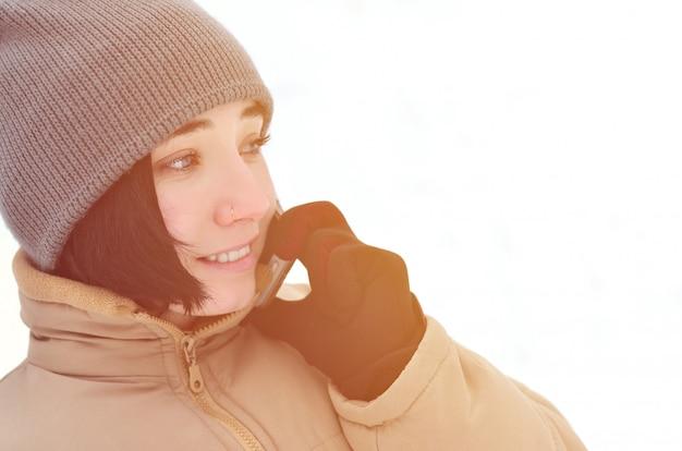 Ritratto di inverno della ragazza con lo smartphone