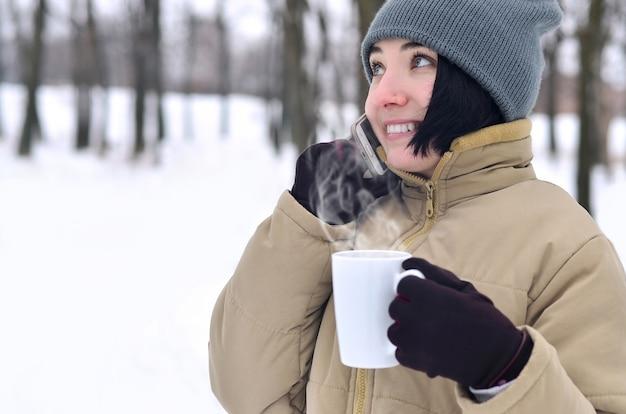 Ritratto di inverno della ragazza con smartphone e tazza di caffè