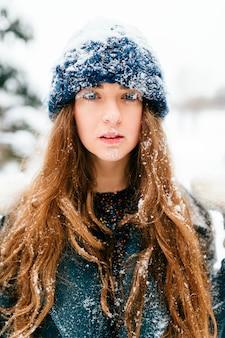 Ritratto di inverno di bella ragazza dai capelli lunghi bruna con il viso e i capelli coperti di neve.