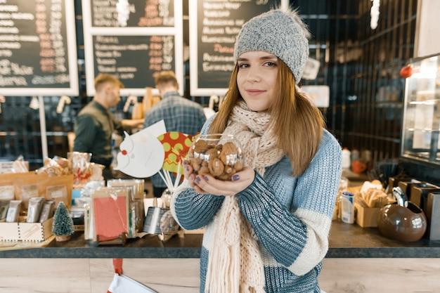 Ritratto di inverno di giovane bella donna in sciarpa lavorata a maglia, cappello lavorato a maglia, guanti, maglione caldo con ciotola di nocciole e noci.
