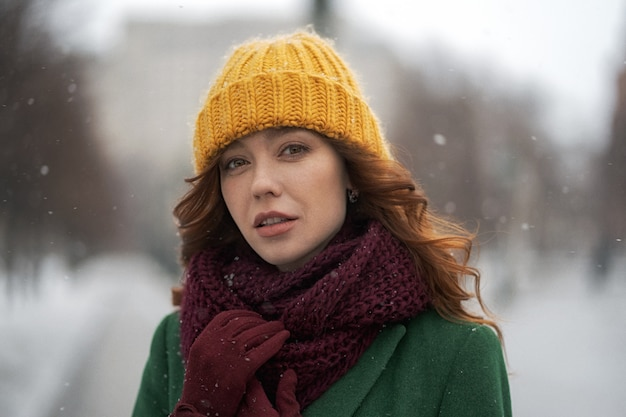 Ritratto di inverno di una bella donna per strada. donna in una baracca gialla sotto la neve