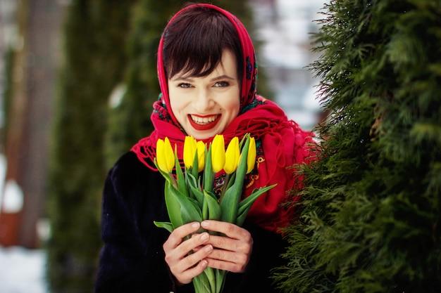 Ritratto di inverno di una ragazza in una sciarpa rossa. in possesso di tulipani