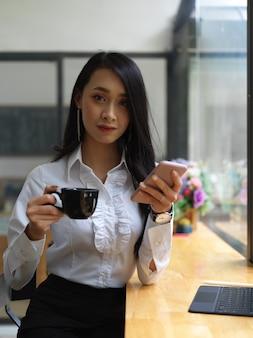 Ritratto di lavoratore di sesso femminile che esamina la macchina fotografica mentre si prende una pausa caffè al bar nella caffetteria