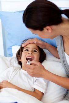 Ritratto di madre che prende la temperatura di suo figlio