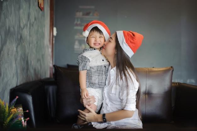 Ritratto di madre felice e piccolo bambino in cappelli di babbo natale